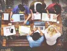 Jeunes adultes qui travaillent sur des ordinateurs et tablettes numériques