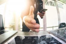 un homme à son bureau tendant la main vers un écran