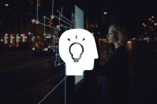 Femme devant un schéma numérique et une illustration d'un visage de profil avec une ampoule
