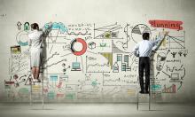 employés d'une start up réalisant le dessin d'une jeune entreprise innovante sur un mur