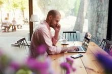 Un homme travaillant de chez lui sur son ordinateur